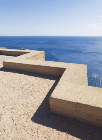 parapet wall: Low stone wall with seascape. The parapet has a zigzag shape and the picture was taken on a sunny day