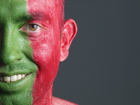 Man with his face painted with the flag of Portugal. The man is smiling and photographic composition leaves only half of the face. photo