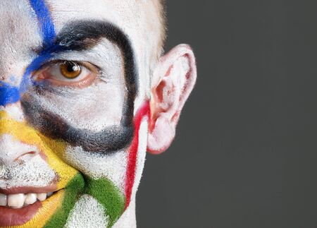Olympic rings painted on the face of man. The man is smiling and isolated on a dark background, looking at camera