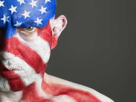 Man with his face painted with the flag of USA. The man is serious and photographic composition leaves only half of the face. photo