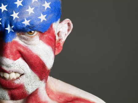 Man with his face painted with the flag of USA  The man is aggressive and photographic composition leaves only half of the face  photo