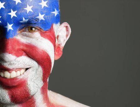 Man with his face painted with the flag of USA  The man is smiling and photographic composition leaves only half of the face  photo