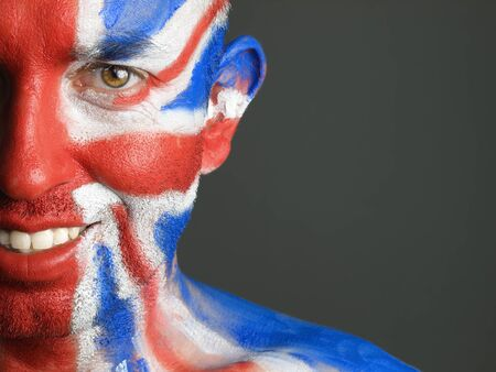 Man with his face painted with the flag of United Kingdom. The man is smiling and photographic composition leaves only half of the face. photo
