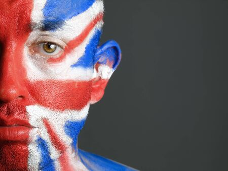 Man with his face painted with the flag of United Kingdom. The man is sad and photographic composition leaves only half of the face. photo