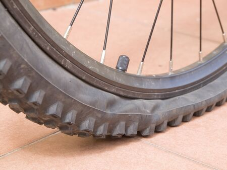 Closeup of a mountain bike wheel. The wheel is flat and has studs photo