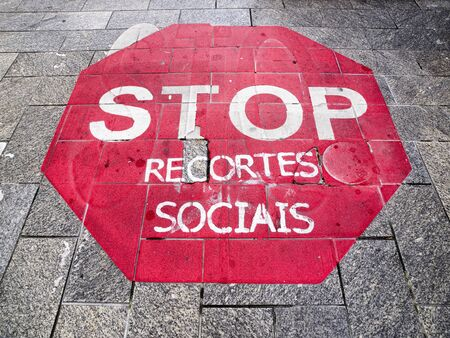 floo: Stop sign on the floor with a Galician language text that refers to the social cuts that are taking place in Spain Stock Photo