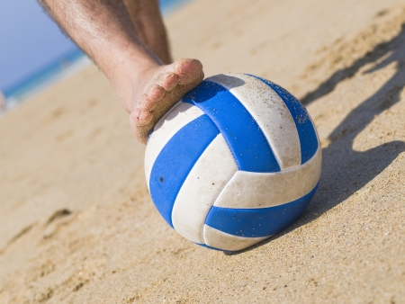 Foot stepping on a ball on the beach. It shows a close-up and the picture was taken at ground level photo