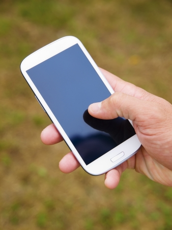 Man hand touching screen on modern mobile smart phone on natural green background