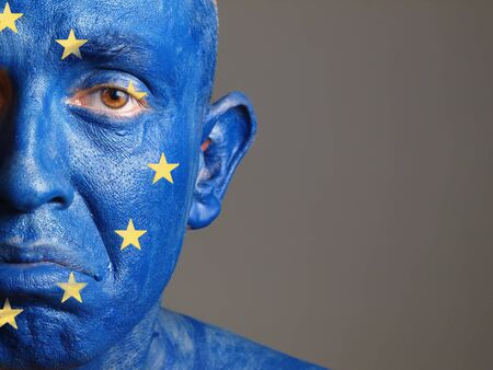 Man with his face painted with the flag of European Union. The man is sad and photographic composition leaves only half of the face. photo