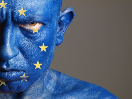 Man with his face painted with the flag of European Union. The man is aggressive and photographic composition leaves only half of the face.