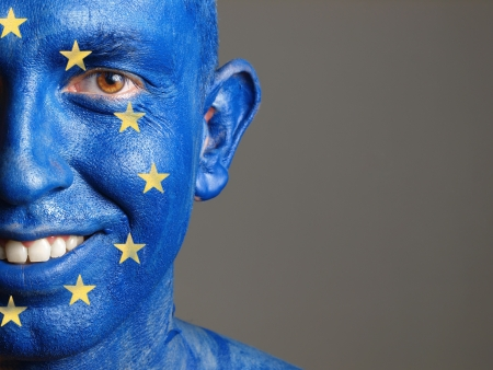 Man with his face painted with the flag of European Union. The man is smiling and photographic composition leaves only half of the face.