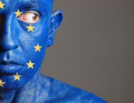 Man with his face painted with the flag of European Union. The man is look sideways and photographic composition leaves only half of the face.