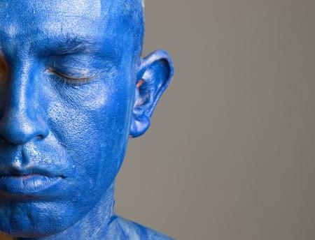 closed eyes: Mens en zijn gezicht beschilderd met kleur blauw. De man is gesloten ogen en fotografische compositie laat slechts de helft van het gezicht.