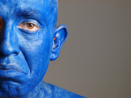 Man with his face painted with color blue. The man is sad and photographic composition leaves only half of the face and he has a sadness expression