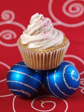 One cupcake and two christmas balls on red background photo