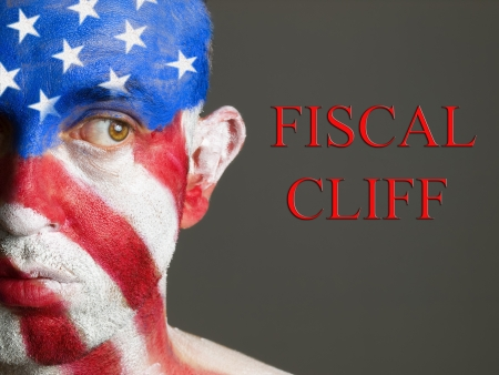 financial cliff: Man with his face painted with the flag of USA. The man is looking at side and he is looking at the phrase
