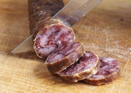 cutting spanish salami slices with a knife Stock Photo