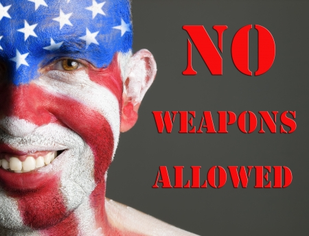 Man with his face painted with the flag of USA. The man is smiling and photographic composition leaves only half of his face. The photo conveys the concept of prohibition of weapons in the U.S. Stock Photo