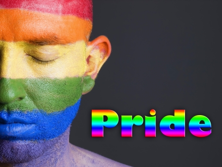 Gay flag painted on the face of a man.The mans eyes are closed with a serene expression on his face. The word pride, is written at one side.