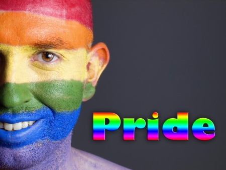 Gay flag painted on the face of a man. Man is looking at camera and is smiling. The word Stock Photo - 16952545