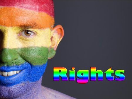 Gay flag painted on the face of a man. Man is looking at camera and is smiling with the word  Stock Photo