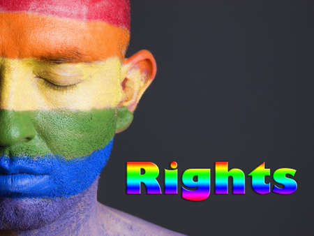 Gay flag painted on the face of a man.The mans eyes are closed with a serene expression on his face. The word rights is written. photo