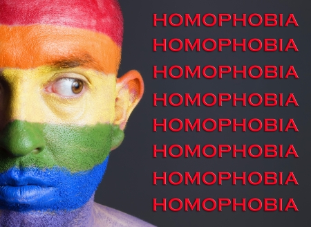 Gay flag painted on the face of a man. Man is looking sideways with restlessness expression. The man is lloking the words