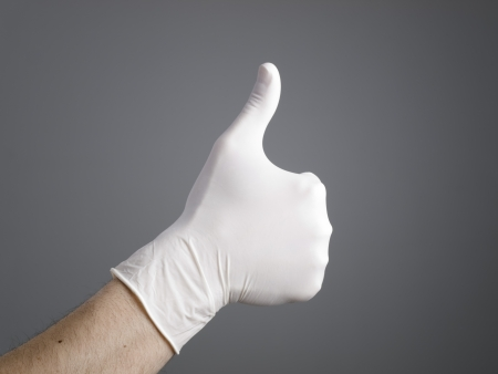 Hand with a latex glove expressing positivity on dark background