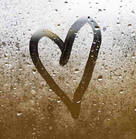 amour: Heart painted on glass  The glass is fogged up and there are many drops on it Stock Photo