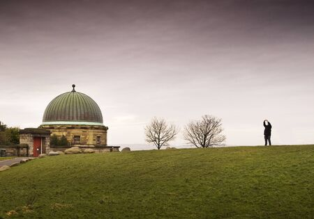 dome building: Dome building in Calton Hill, Edinburgh  There are two leafless trees and one person, the sky is overcast