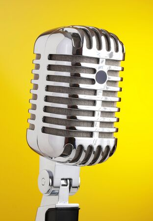 Microphone metal yellow background  The photo shows a classic microphone isolated on a yellow background  photo