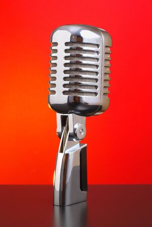 Classic microphone on red background photo