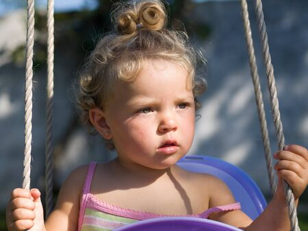 Little girl on a swing in a sunny day photo