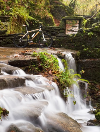 Small waterfall with bicycle in nature  A beautiful place  photo
