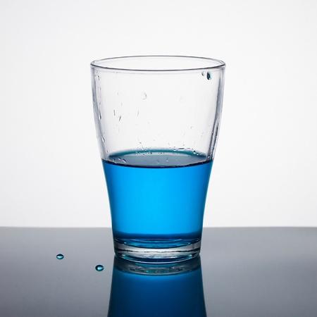 Glass half full of blue liquid on light background