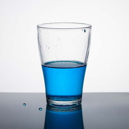 Glass half full of blue liquid on light background