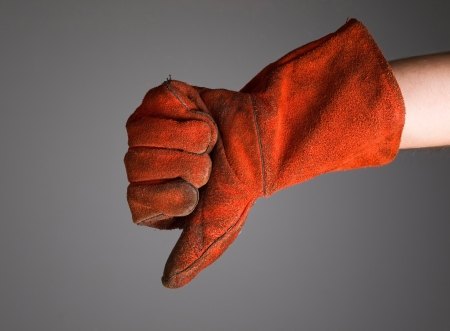 expressing negativity: Hand expressing negativity with welder glove isolated on dark background