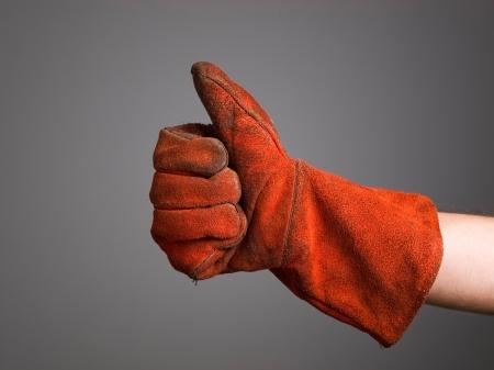 Hand expressing positivity with welder glove isolated on dark background Standard-Bild