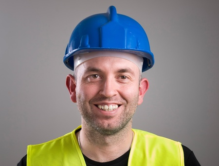 Portrait of a worker expressing positivity isolated on dark background photo