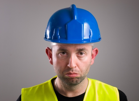 Portrait of a worker expressing negativity and isolated on dark background photo