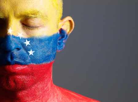 Man and his face painted with the flag of Venezuela photo