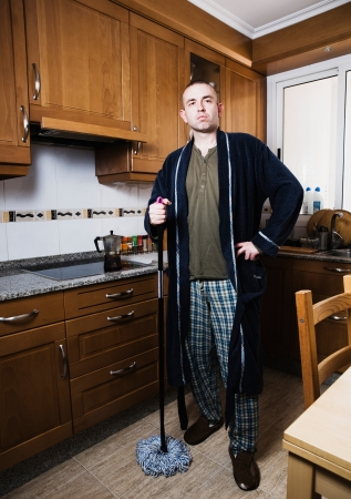 lifestile: The man is standing with a mop in hand and with a casual dress  Stock Photo