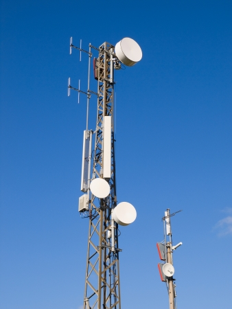 Two telecommunications antennas on blue sky photo