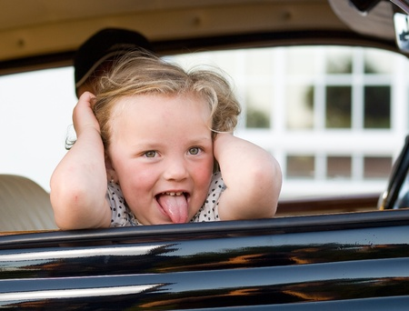 Little girl leaning out the window of a car with a funny expression photo