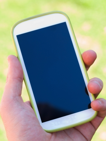 Hand holding a smart phone on natural green background photo