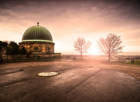 Dome building and Calton Hill, Edinburgh. There are two leafless trees and the sun is setting in the horizon photo