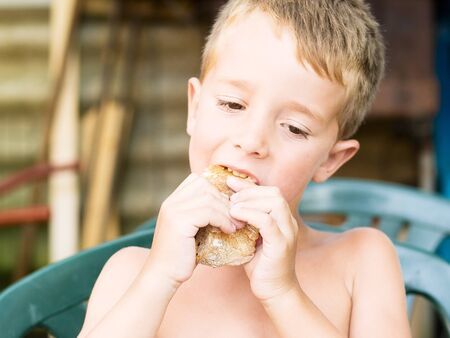 Little boy eating a sandwich outdoors  in a summer day photo
