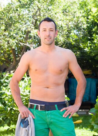 notion: Adult man posing shirtless for a photo outdoors