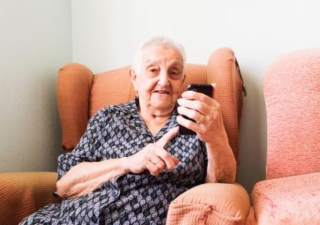 Oude dame met behulp van een smartphone in haar huis