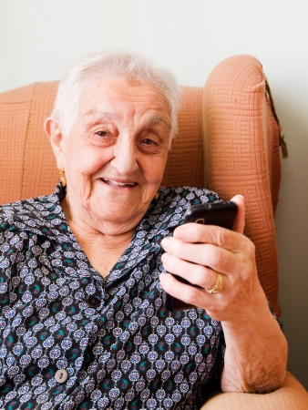 old woman with a smart phone and smiling inside her home. photo